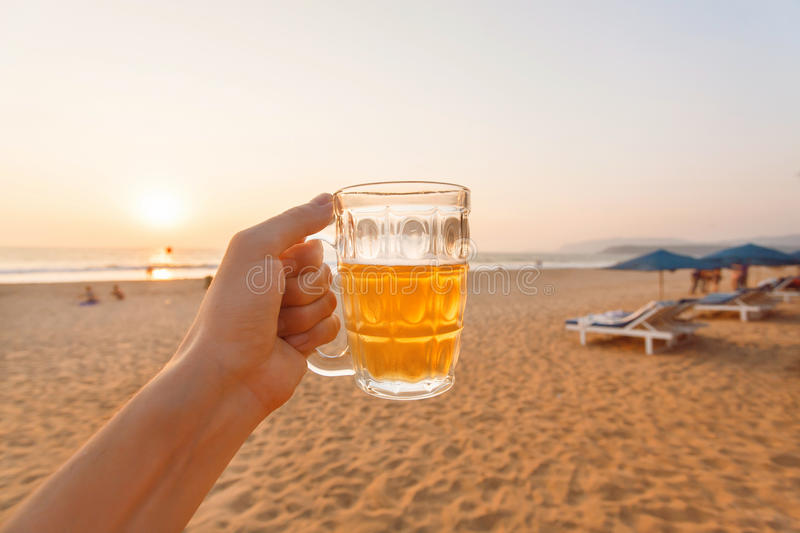 Sunset over sandy beach and one glass of cold beer in hand of happy tourist. stock images