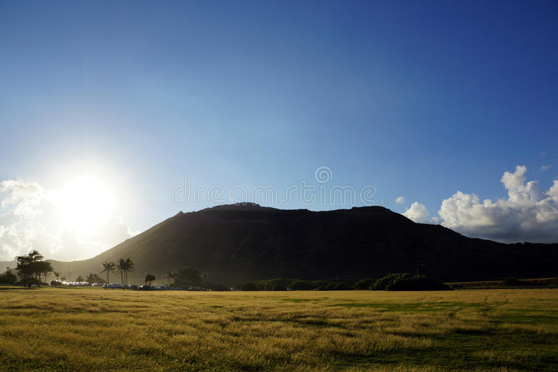 Sunset over Sandy Beach Park grass field and Koko Head Crater. In the distance on Oahu, Hawaii. 2013 royalty free stock photos
