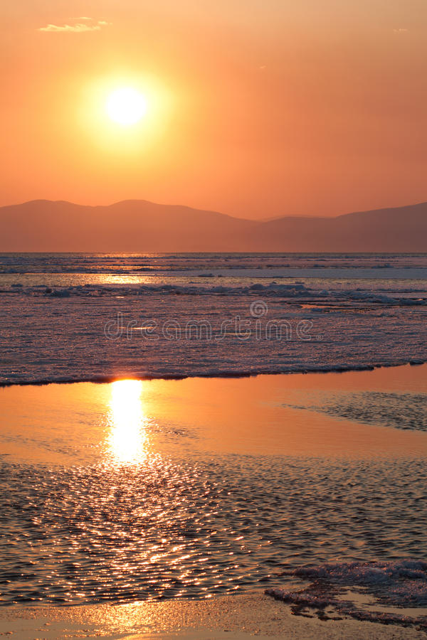 Sunset over the sea with breaking ice. stock images