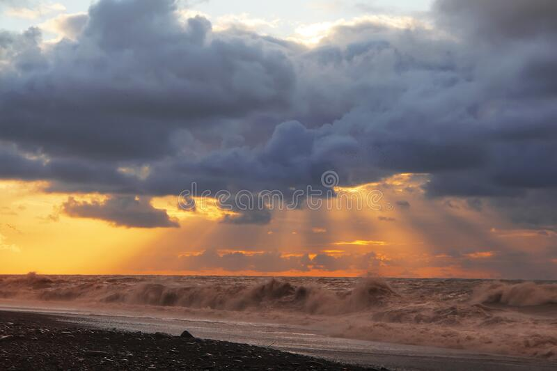 Sunset over sea with dramatic sky sky, dark storm clouds, and red light royalty free stock image