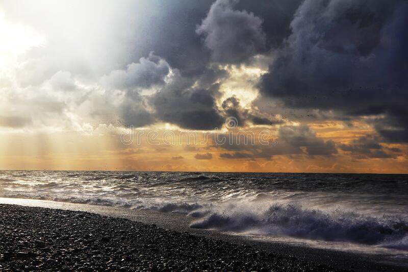 Sunset over sea with dramatic sky sky, dark storm clouds, and red light royalty free stock photography