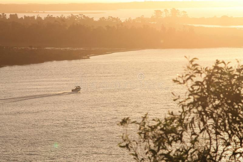 Sunset over the sea. Hot summers night at the beach in Lakes Entrance Australia. boat heading towards the entrance along the channel. taken from the Kalimna stock photography