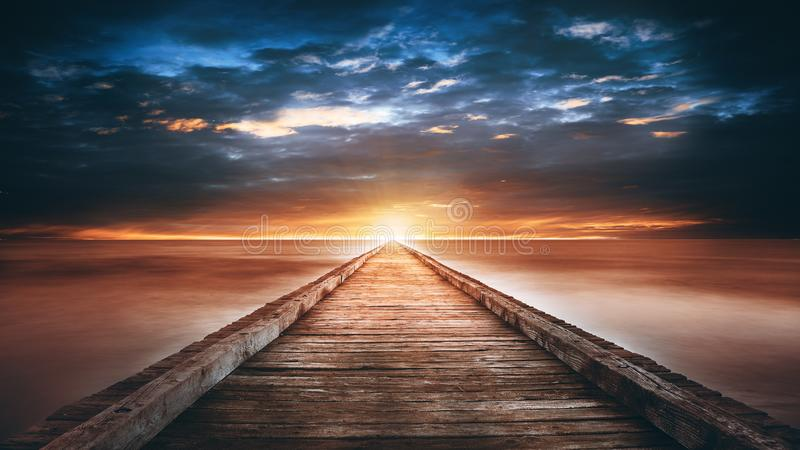 Sunset over the sea. Pier on the foreground. Mysterious view stock image