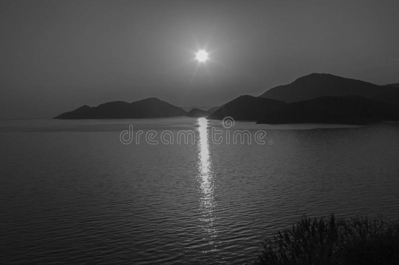 Sunset over the sea. Reflection of the solar track on the surface of the sea. On the horizon - the mountains. Black and white.. Sunset over the sea. Reflection stock photos