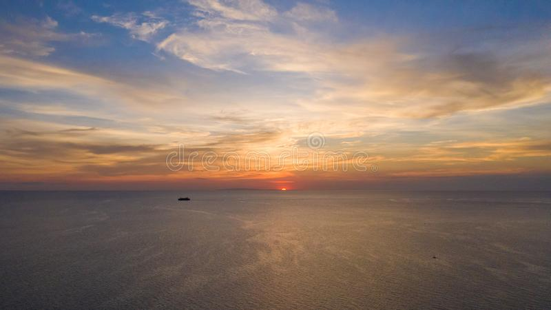 Sunset over the sea and sailing ship in the distance stock image