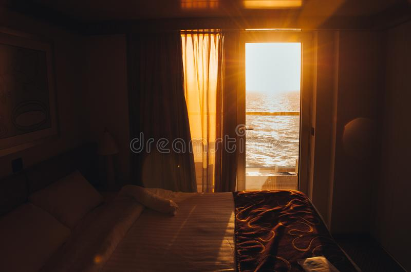 Sunset over the sea seen from inside the cabin of a cruise ship stock photo