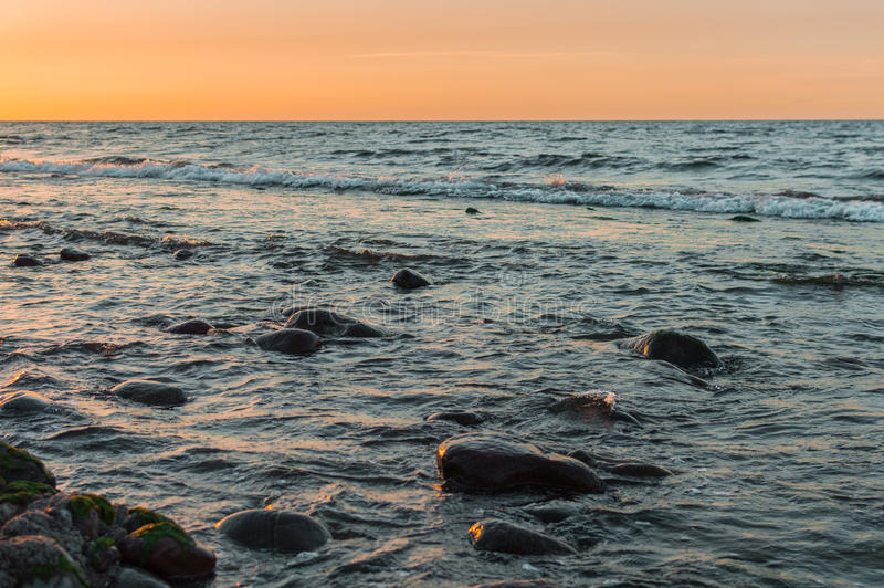 Sunset over the sea. Stone on the foreground. Sunset over the sea. Stone on the foreground stock photography
