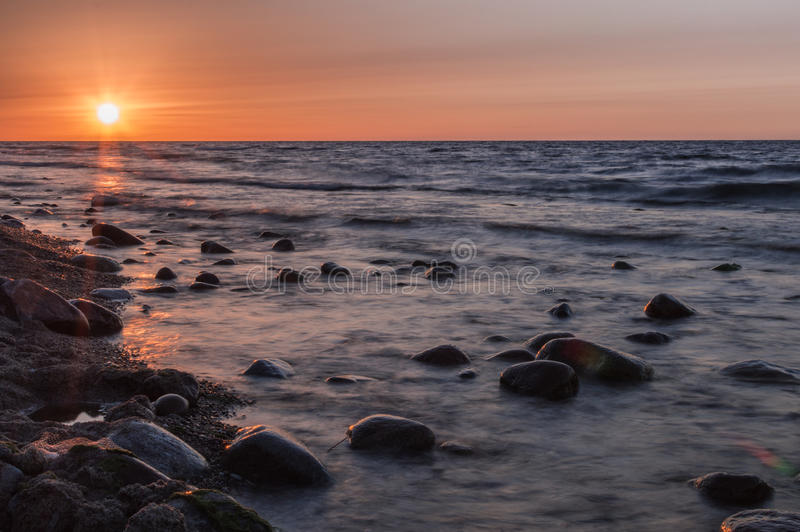 Sunset over the sea. Stone on the foreground. Sunset over the sea. Stone on the foreground stock photo