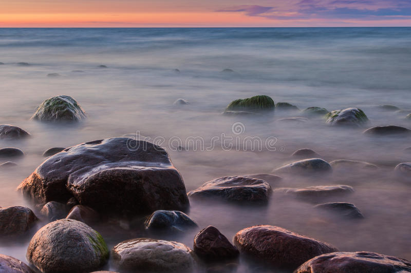 Sunset over the sea. Stone on the foreground. Sunset over the sea. Stone on the foreground royalty free stock photos