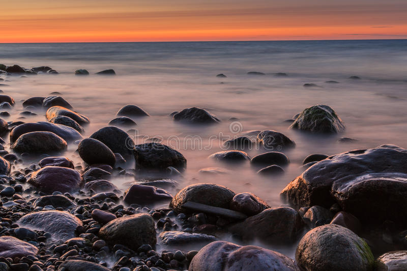 Sunset over the sea. Stone on the foreground. Sunset over the sea. Stone on the foreground stock image