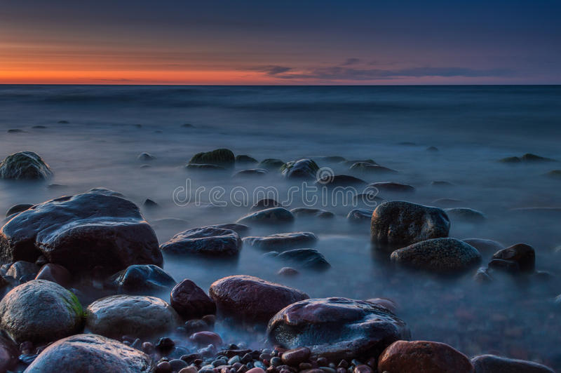 Sunset over the sea. Stone on the foreground. Sunset over the sea. Stone on the foreground royalty free stock photography