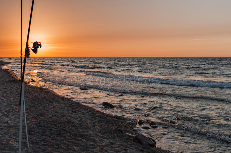 Sunset over the sea. Stones and fishing rods on the foreground.  royalty free stock photo