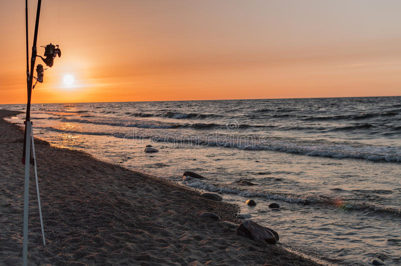 Sunset over the sea. Stones and fishing rods on the foreground.  royalty free stock photography
