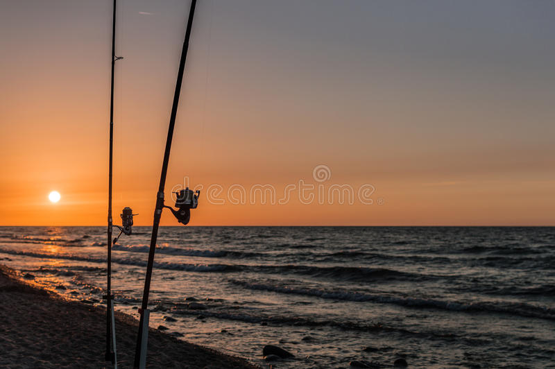 Sunset over the sea. Stones and fishing rods on the foreground.  royalty free stock photos
