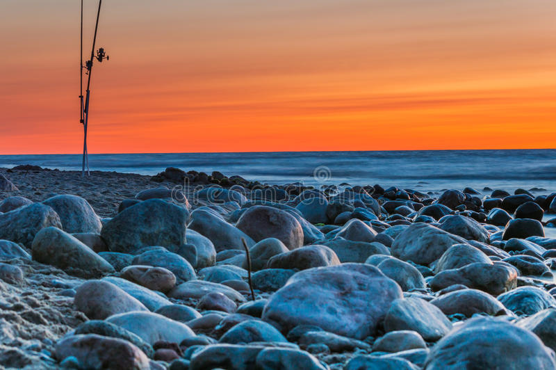 Sunset over the sea. Stones and fishing rods on the foreground.  royalty free stock images