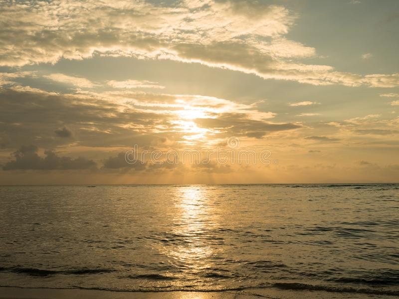 Sunset over sea. Sun light reflect with sea wave surface and flare. Summer time for vacation and holiday.  stock photography