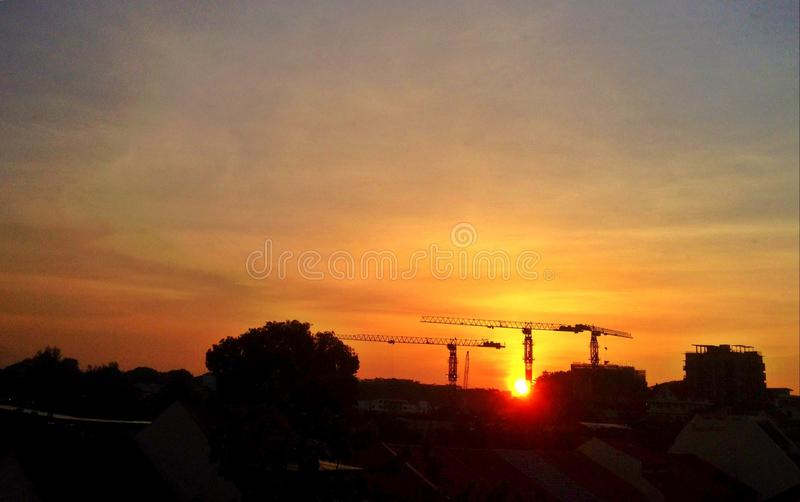 Sunset over silhouette of buildings. Evening sky above cranes of buildings under construction in Singapore stock images