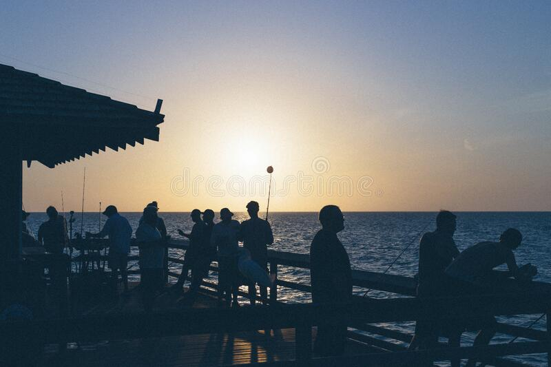 Sunset Over Silhouette Of People Near Body Of Water Free Public Domain Cc0 Image