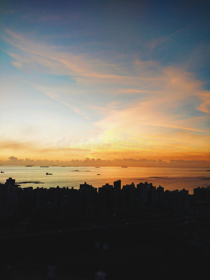 Sunset over silhouetted city skyline royalty free stock photos