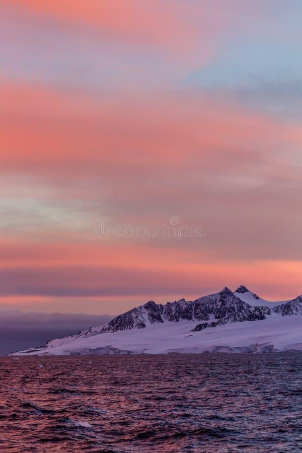 Sunset over snow and sharp mountain peaks in Weddel Sea near Antarctica Peninsula stock image