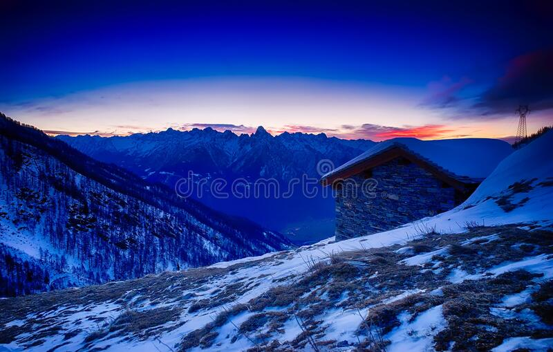 Sunset over snowy mountain cabin stock photography