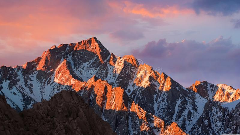 Sunset over snowy mountains stock photos