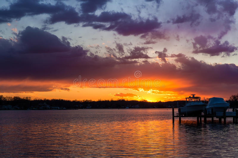 Sunset over the South River in Maryland. The setting sun ignites hues across the sky during the gorgeous sunset over the South River and the boating community of stock photos