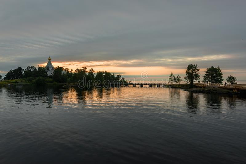 Sunset over the St. Nicholas monastery and the water surface of lake Ladoga. Valaam is a cozy and quiet piece of land, the rocky shores of which rise above the stock photos