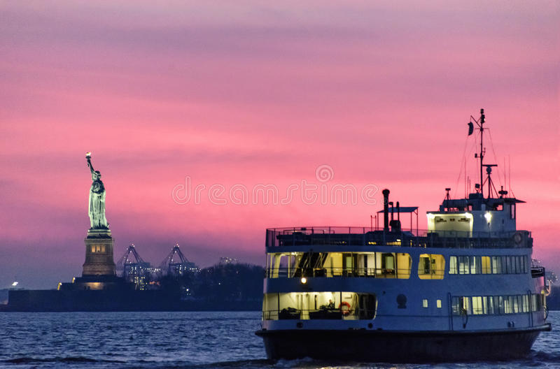 Sunset Over Statue of Liberty. Silhouette of the Statue of Liberty and a sailboat during a beautiful sunset stock image