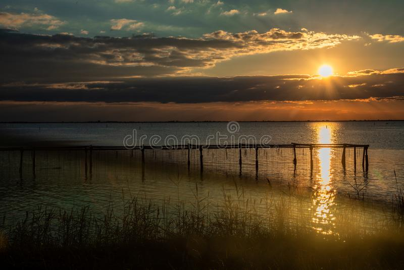 Sunset over Stilt house and fishing nets along the Po Delta. Italy royalty free stock photo