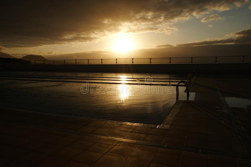 Sunset over swimming pool royalty free stock images