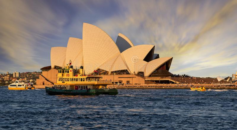 Sunset over Sydney Opera House from Sydney Harbour with ferry in foreground stock photography
