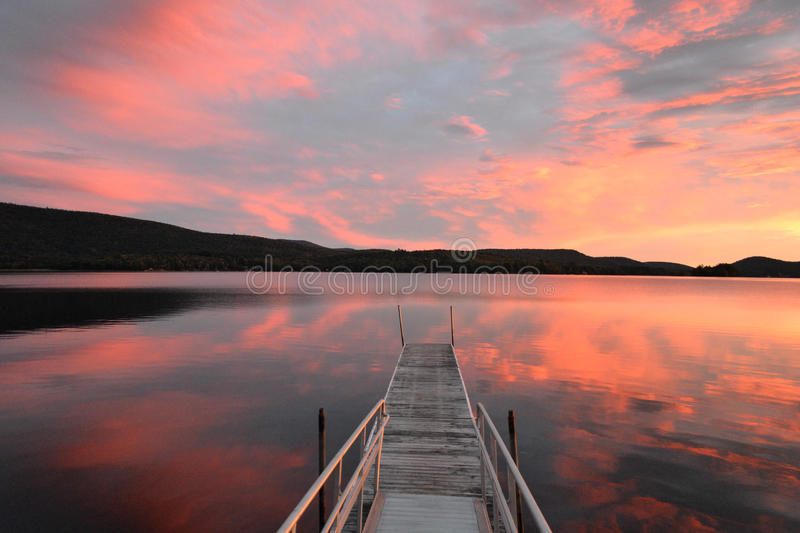 Sunset Over Tranquil Mountain Lake. Sunset (or sunrise) over tranquil Adirondack Mountain lake in upstate New York (Lake Pleasant). Good for vacation, sense of stock photos