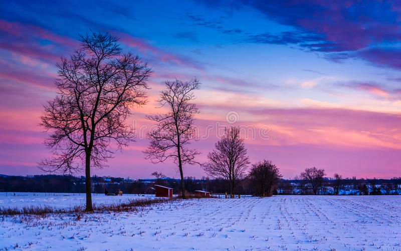 Sunset over trees and snow covered farm fields in rural Frederic royalty free stock photos
