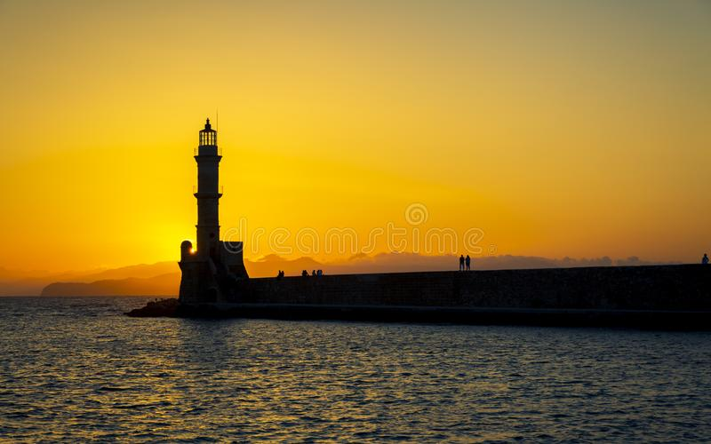 Sunset over The Venetian era harbour walls and lighthouse at the Mediterranean port of Chania. Canea, Crete, Greek Islands, Greece, Europe stock photos