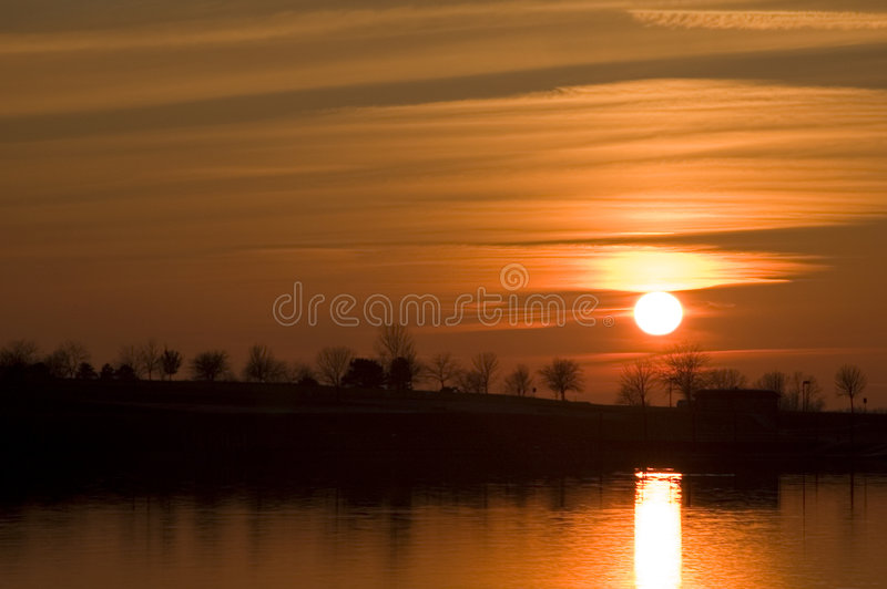Sunset over water. Beautiful orange sunset over water with reflection of sun on surface of water royalty free stock photos