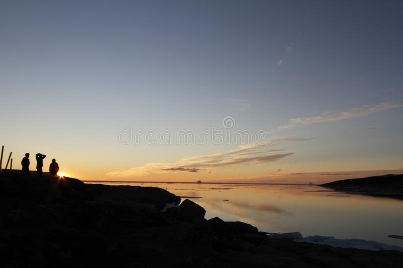 Sunset over water with three people in the shadow with whisp of clouds stock photos
