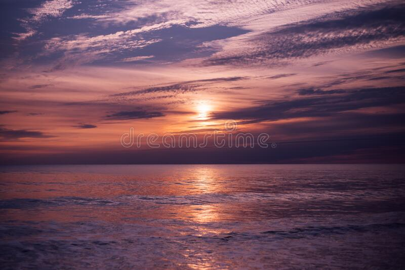 Sunset over waves on ocean stock images