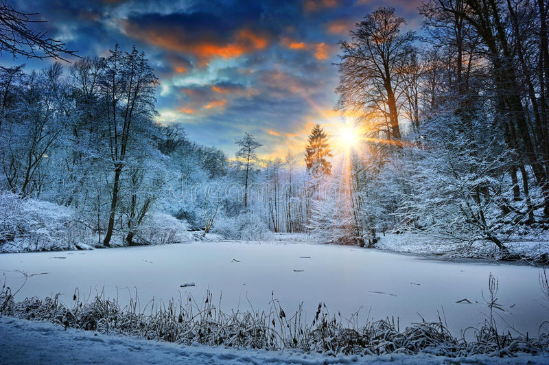 Sunset over winter forest lake stock images