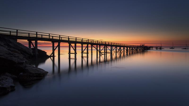 Sunset over wooden pier royalty free stock photos
