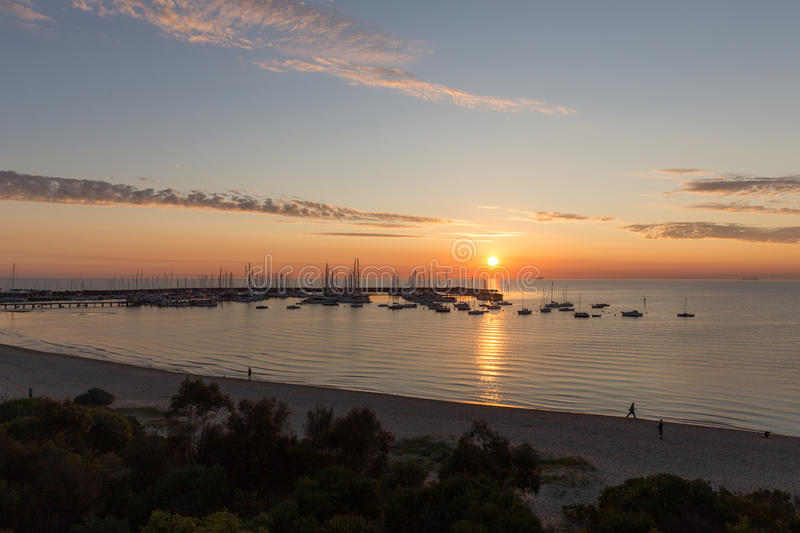 Sunset over yacht club. With golden coloured clouds and foreground with people in hampton melbourne australia royalty free stock images