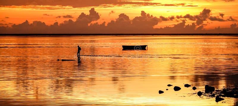Sunset på ön Mauritius med en silhuett av en icke igenkännlig fiskare som går hem efter en fiskedag - Berlusen och resa fotografering för bildbyråer