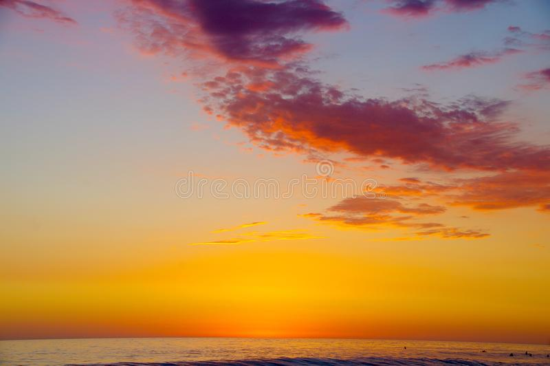 Sunset at the Pacific Ocean with surfers and swimmers. A vast sky is set ablaze with a sunset of orange, gold, yellow, pink, purple and blue over a seemingly royalty free stock image