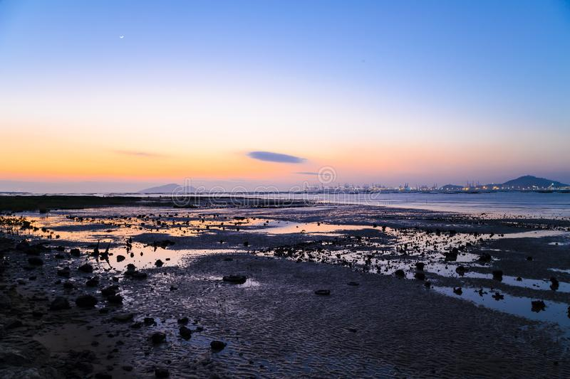 Sunset at the Pak Nai wetland area. Pak Nai is a wetland area, partly mud-bank, surrounded by mountain ranges, in the Yuen Long District of Hong Kong facing Deep royalty free stock photos