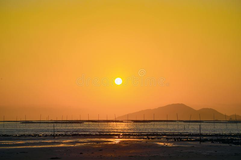 Sunset at the Pak Nai wetland area. Pak Nai is a wetland area, partly mud-bank, surrounded by mountain ranges, in the Yuen Long District of Hong Kong facing Deep royalty free stock photo