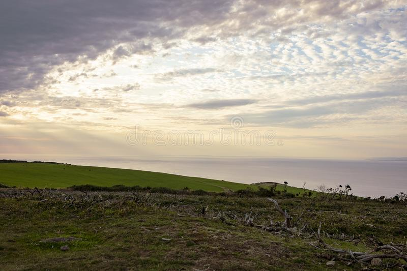 Evening cloudy sky over scenic Somerset coast. Summer Rural English landscape. Sunset sky. View on Bristol Channel, green meadows, royalty free stock images
