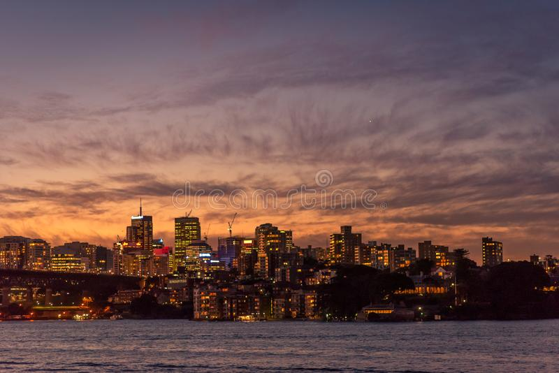A sunset panoramic of buildings and skyscrapers at Sydney Harbour, on the far side of the bridge royalty free stock photography