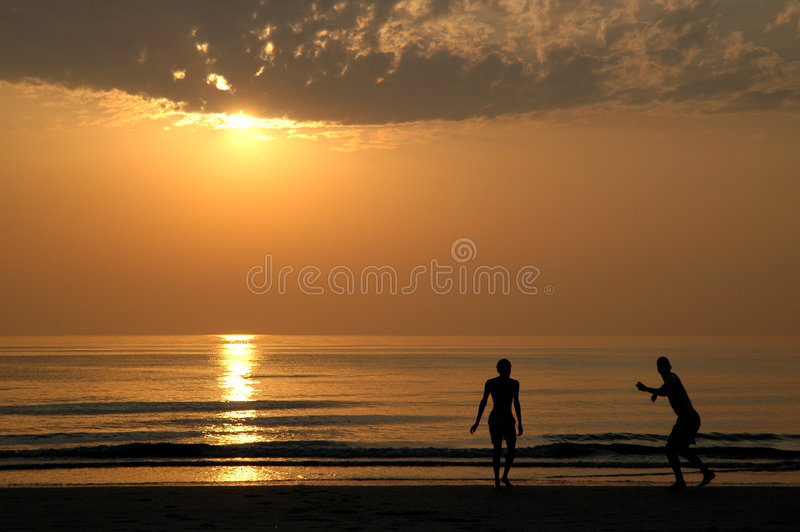 Sunset with people. Who are playing on the beach stock photo