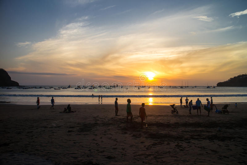 Sunset with people on beach from San Juan del Sur, Nicaragua. San Juan del Sur, Nicaragua March 9, 2016 sunset with people on beach stock image
