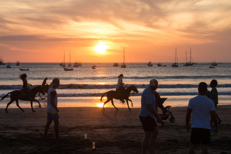 Sunset with people on beach from San Juan del Sur, Nicaragua. San Juan del Sur, Nicaragua on March 9, 2016 sunset with people on beach stock image